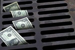 Dollar bills in a street drain