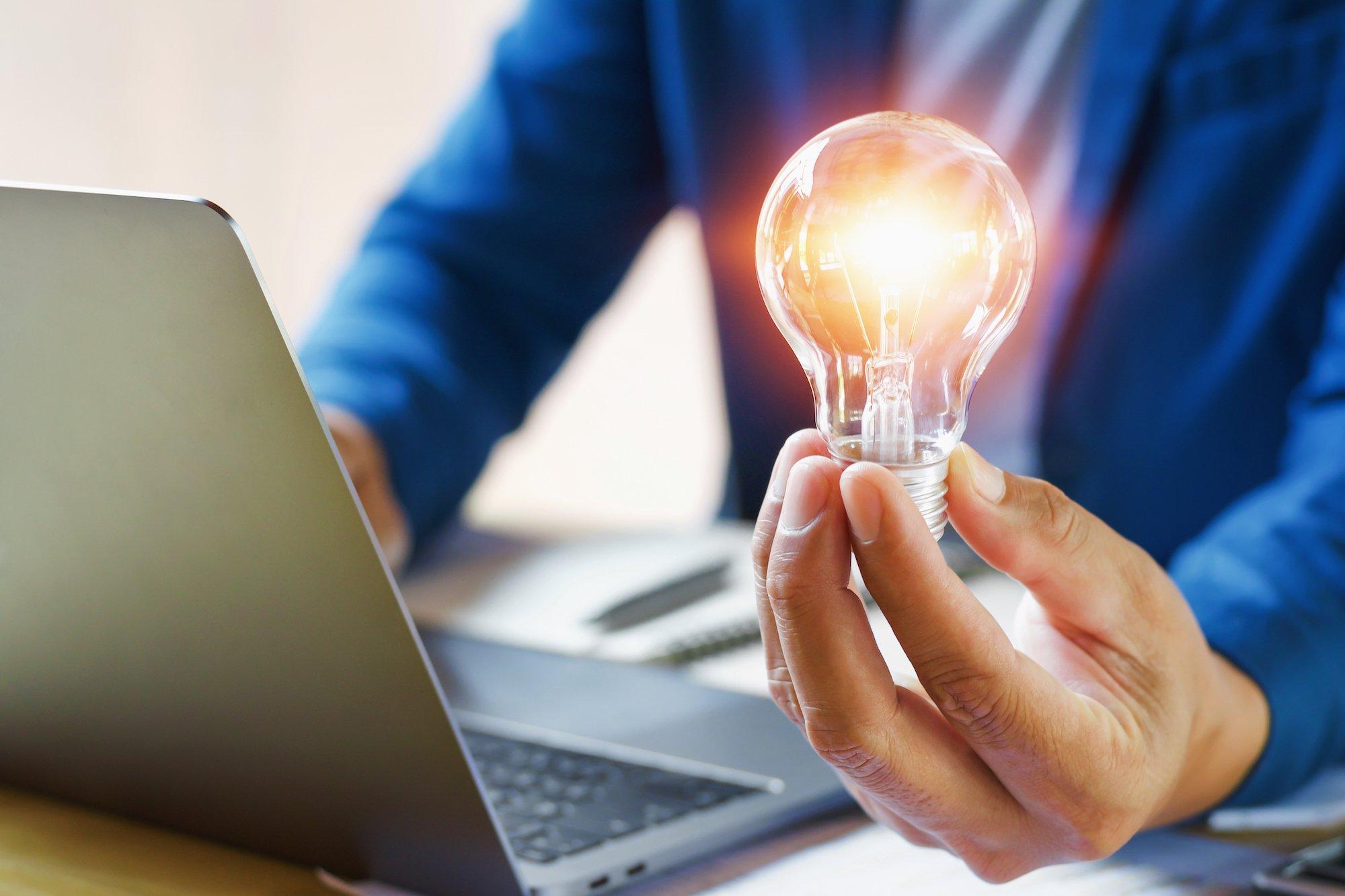 ASX Energy origin-energy-org-asx-businessman holding lightbulb in office. creative idea for saving energy. concept finance and accounting