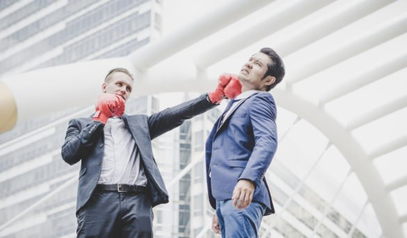 ansell-ann-share-priceBusinessman with red boxing gloves ready to fight his coworker.