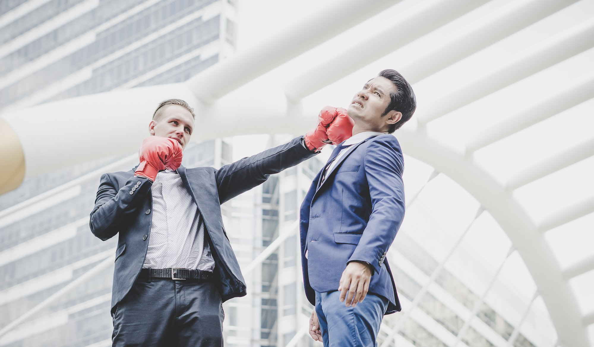 credit-corp-ansell-ann-share-priceBusinessman with red boxing gloves ready to fight his coworker.