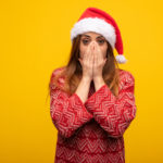 ann-share-price-Young woman wearing santa hat very scared and afraid hidden